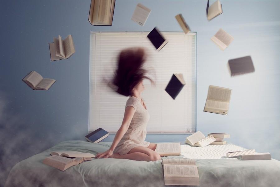 女性と飛び舞う本の画像
